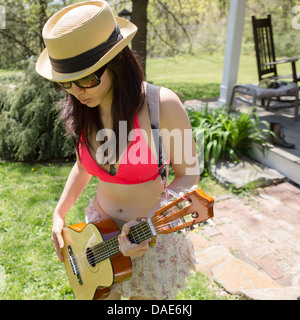 Woman wearing hat playing guitar - Stock Photo