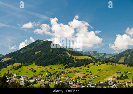 panoramic view over the mountain village in the Kleinwalsertal with the Heuberg (1795 m) in the background, Austria, - Stock Photo