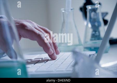 Scientist using laptop in laboratory - Stock Photo