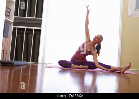 Woman sitting on floor with arm raised - Stock Photo
