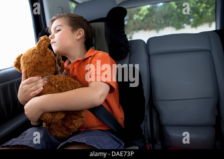 Boy looking out of car window holding teddy bear - Stock Photo