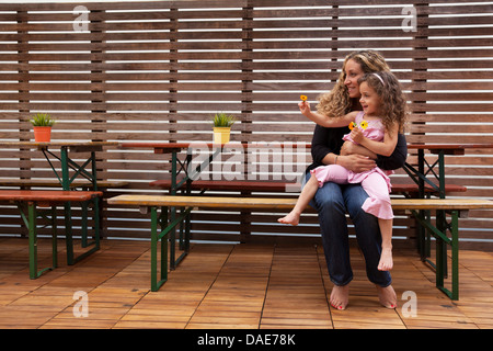 Mother and daughter sitting on bench on patio - Stock Photo