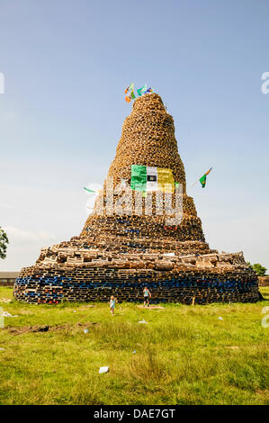 Newtownabbey, Northern Ireland. 11th July 2013. Children play at the bottom of a very large bonfire, estimated to - Stock Photo