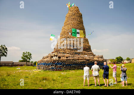 Newtownabbey, Northern Ireland. 11th July 2013. People gather to see an enormous bonfire, estimated at over 30m - Stock Photo