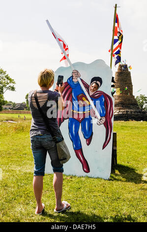 Newtownabbey, Northern Ireland. 11th July 2013. A mother takes a photograph of her son through a Superman cutout - Stock Photo