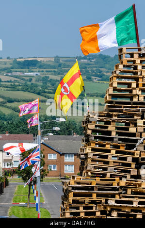 Newtownabbey, Northern Ireland. 11th July 2013. Irish flags on top of Ballyduff bonfire, and UVF, Unionist and Union - Stock Photo