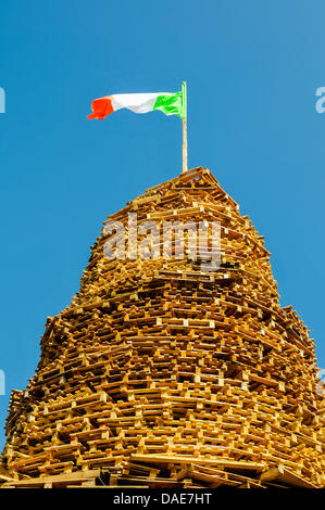 Newtownabbey, Northern Ireland. 11th July 2013.  The Irish Tricolour flag flys on top of a loyalist bonfire ready - Stock Photo