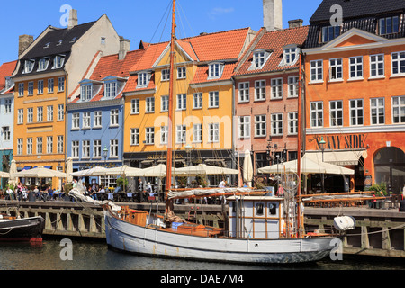 Old wooden boat on canal with cafes and colourful buildings on 17th century waterfront in Nyhavn harbour Copenhagen - Stock Photo