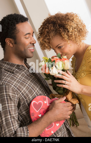 Man giving woman flowers and chocolates on valentines day - Stock Photo