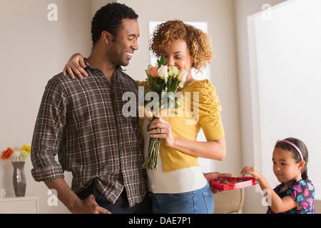 Man giving woman flowers, daughter taking chocolate - Stock Photo