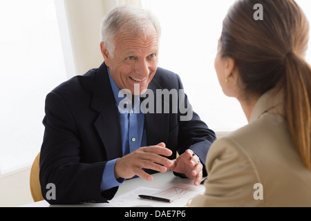 Man and woman talking in meeting - Stock Photo