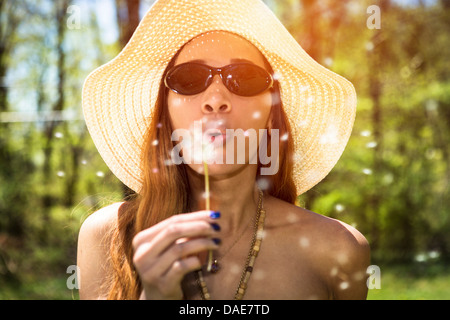 Woman blowing dandelion clock - Stock Photo