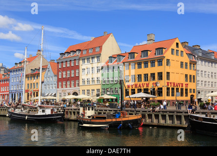 Old wooden boats moored on canal by colourful 17th century buildings on waterfront busy with people in old city. - Stock Photo