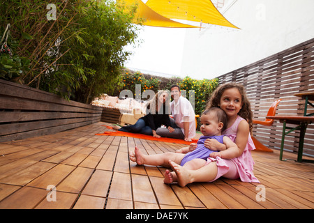 Girl with baby sister sitting on lap, parents in background - Stock Photo