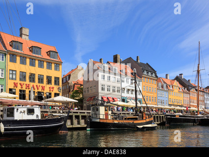 Old wooden boats moored on canal by colourful 17th century buildings on waterfront in Nyhavn harbour, Copenhagen, - Stock Photo
