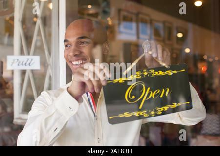 Shopkeeper turning open sign on vintage shop door - Stock Photo