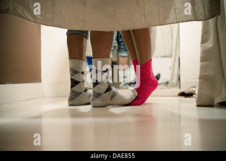 Young couple wearing socks in changing room, low section - Stock Photo