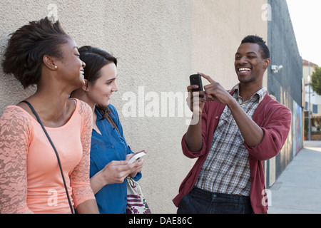 Young man photographing female friends on cell phone - Stock Photo