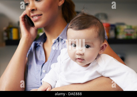 Mother holding baby girl whilst on the phone - Stock Photo