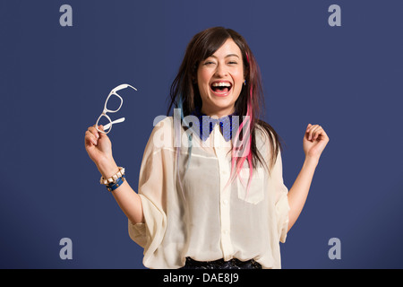 Portrait of young woman with dyed hair holding glasses