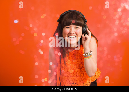 Portrait of young woman wearing headphones - Stock Photo