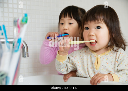 Two girl toddlers brushing teeth at bathroom sink - Stock Photo
