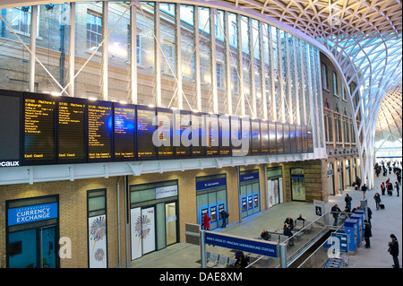 Departure boards in the western concourse area of Kings Cross Railway Station, London, England. - Stock Photo