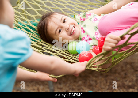 Young girl in hammock with colored balls - Stock Photo