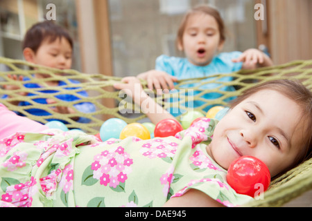 Portrait of young girl in hammock with colored balls - Stock Photo
