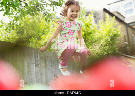 Young girl jumping mid air in garden - Stock Photo