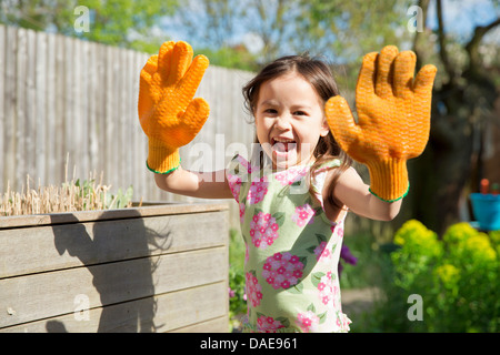 Young girl in garden wearing oversized gloves - Stock Photo