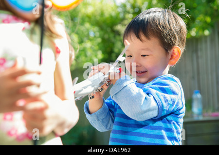 Male toddler in garden with toy airplane - Stock Photo