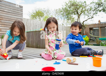 Three young children painting and drawing in garden - Stock Photo