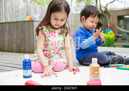 Young brother and sister painting and drawing in garden - Stock Photo