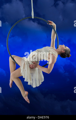 Aerialist performing on hoop against blue background - Stock Photo