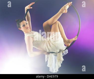 Aerialist poised on hoop against purple background - Stock Photo