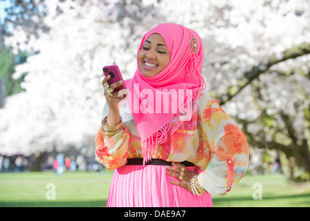 Young woman in park wearing pink headscarf and skirt - Stock Photo