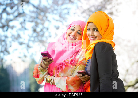 Portrait of two young woman in park with mobile phones - Stock Photo