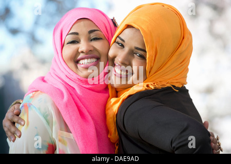 Close up portrait of two young woman in park - Stock Photo