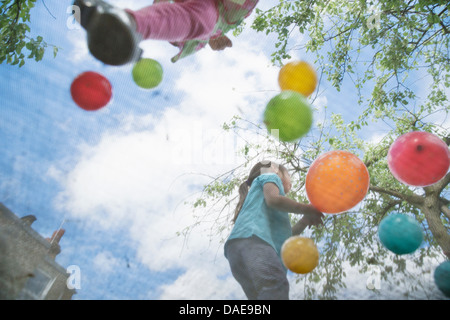 Young girls jumping on garden trampoline - Stock Photo