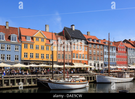 Wooden boats moored on canal with cafes and colourful buildings on waterfront in Nyhavn harbour Copenhagen Zealand - Stock Photo