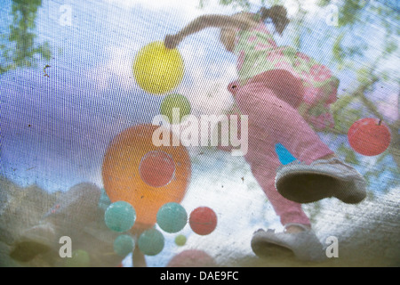 Young girls bouncing on garden trampoline - Stock Photo