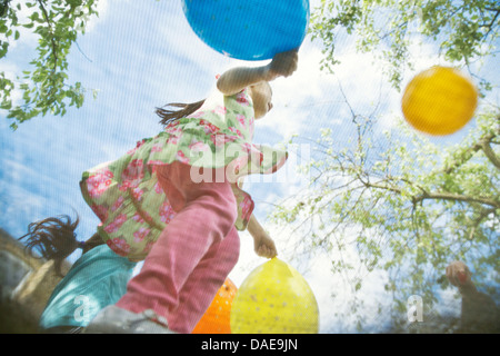 Young girls bouncing on garden trampoline with balloons - Stock Photo
