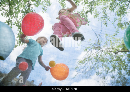 Young girls jumping on garden trampoline with balloons - Stock Photo