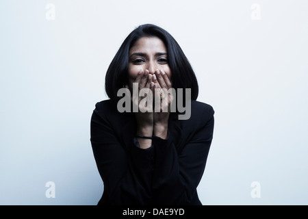 Studio portrait of businesswoman with hands over mouth - Stock Photo