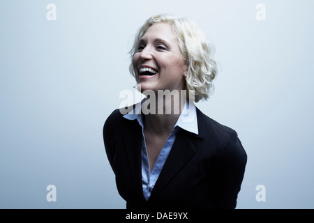 Studio portrait of businesswoman laughing - Stock Photo