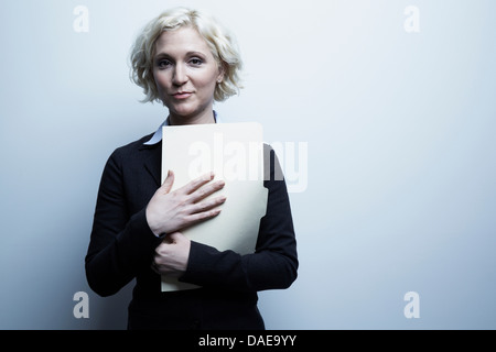 Studio portrait of businesswoman holding file - Stock Photo