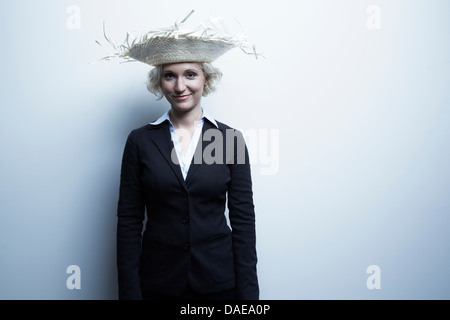 Studio portrait of blond businesswoman wearing straw hat - Stock Photo