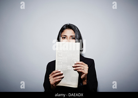 Studio portrait of businesswoman holding up newspaper - Stock Photo