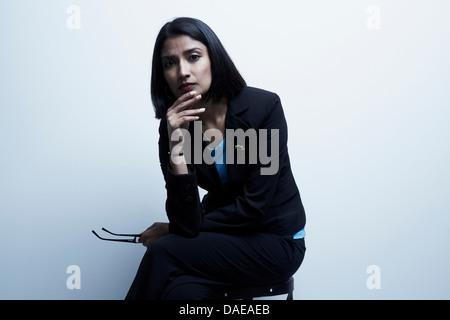 Studio portrait of businesswoman holding spectacles - Stock Photo